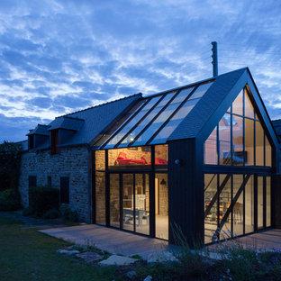 Diseño de fachada beige, contemporánea, grande, de dos plantas, con revestimiento de vidrio y tejado a dos aguas