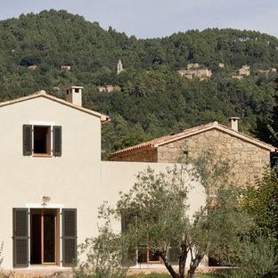 Inspiration pour une façade de maison beige traditionnelle de taille moyenne et à un étage avec un toit à deux pans.