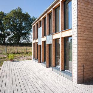 Aménagement d'une grande façade en bois marron contemporaine à un étage avec un toit à deux pans.