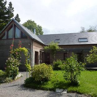 Cette photo montre une façade en bois marron nature de taille moyenne et à un étage avec un toit à deux pans.