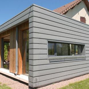 Cette image montre une petit façade métallique grise design de plain-pied avec un toit plat.