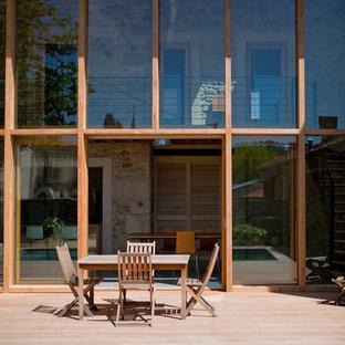 Cette photo montre une façade en verre marron tendance de taille moyenne et à un étage avec un toit à deux pans.