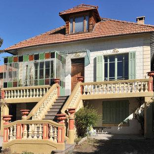 Réalisation d'une façade de maison bohème à un étage et de taille moyenne avec un toit à quatre pans.