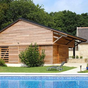 Idées déco pour une grand façade de maison marron campagne de plain-pied avec un toit à deux pans et un toit en tuile.