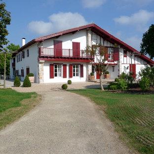 Idée de décoration pour une façade de maison blanche champêtre de taille moyenne et à un étage avec un revêtement mixte et un toit à deux pans.