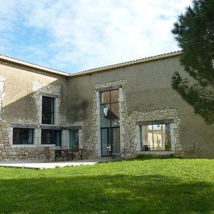 Cette photo montre une façade en pierre beige nature de taille moyenne et à un étage avec un toit à deux pans.