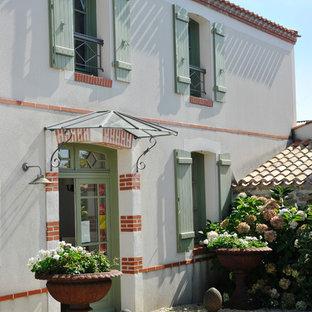 Inspiration pour une façade de maison blanche traditionnelle à un étage et de taille moyenne avec un toit à deux pans.