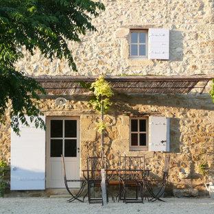 Cette image montre une façade en pierre beige rustique de taille moyenne et à un étage.