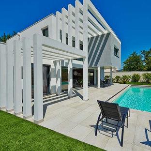 Aménagement d'une façade de maison grise contemporaine à un étage avec un toit plat.