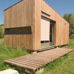 Idée de décoration pour une façade en bois marron design de taille moyenne et de plain-pied avec un toit plat.