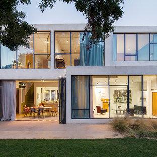 Exemple d'une grand façade en béton grise tendance à un étage avec un toit plat.