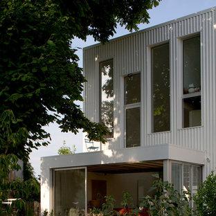 Cette image montre une façade métallique blanche design de taille moyenne et à deux étages et plus avec un toit plat.