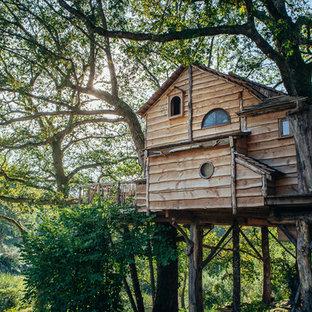 Ejemplo de fachada marrón, rural, de tamaño medio, de dos plantas, con revestimiento de madera y tejado a dos aguas