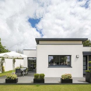 Cette photo montre une façade de maison blanche tendance de plain-pied avec un revêtement en stuc et un toit plat.