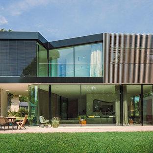Exemple d'une façade de maison noire moderne à un étage avec un revêtement mixte et un toit plat.
