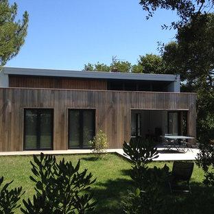 Idée de décoration pour une façade en bois marron design de taille moyenne et à un étage avec un toit plat.