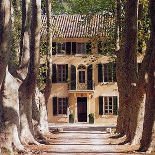 Inspiration pour une grand façade de maison beige traditionnelle à deux étages et plus avec un revêtement en stuc et un toit à deux pans.