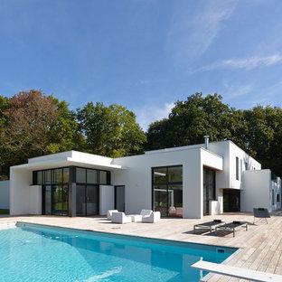 Idées déco pour une façade de maison blanche contemporaine de plain-pied avec un revêtement en stuc et un toit plat.