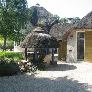 Idées déco pour une façade de maison beige campagne de taille moyenne et à un étage avec un toit à quatre pans.