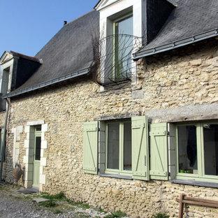 Réalisation d'une façade en pierre beige design de taille moyenne et à un étage avec un toit à deux pans.