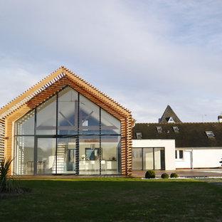 Aménagement d'une façade de maison blanche contemporaine avec un revêtement mixte et un toit à deux pans.