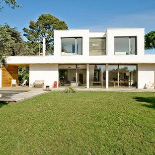 Idée de décoration pour une grande façade de maison blanche minimaliste à un étage avec un toit plat.