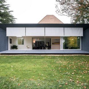 Réalisation d'une façade en verre grise design de plain-pied et de taille moyenne avec un toit plat.