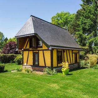 Exemple d'une petit façade de maison jaune chic à un étage avec un revêtement en adobe et un toit à croupette.