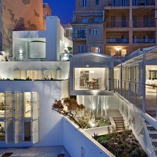 Réalisation d'une façade de maison blanche design de taille moyenne et à deux étages et plus avec un toit plat.