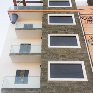 Esempio della facciata di un appartamento grande beige contemporaneo a tre o più piani con rivestimenti misti, tetto piano e copertura mista
