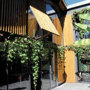 Réalisation d'une façade en bois marron design de taille moyenne et à un étage avec un toit à deux pans.