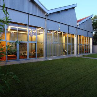 Idée de décoration pour une grande façade métallique grise design à un étage avec un toit en appentis.