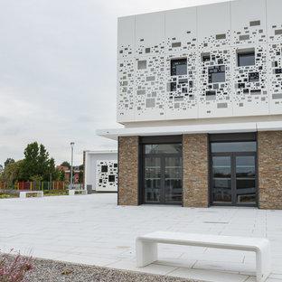 Ejemplo de fachada de piso multicolor, contemporánea, de tamaño medio, de tres plantas, con revestimiento de piedra