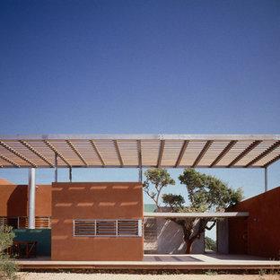Inspiration pour une façade de maison rouge méditerranéenne de taille moyenne et de plain-pied avec un revêtement mixte et un toit plat.