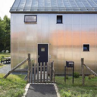 Imagen de fachada gris, de estilo de casa de campo, de dos plantas, con revestimiento de vidrio y tejado a dos aguas