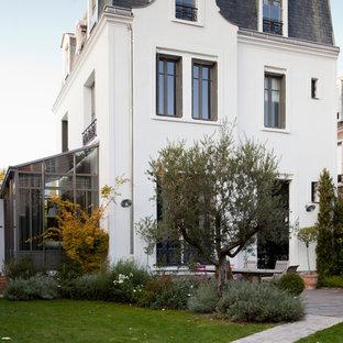 Inspiration pour une grand façade de maison blanche traditionnelle à deux étages et plus avec un toit à quatre pans.