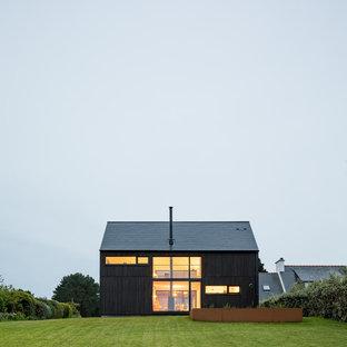 他の地域の中くらいのインダストリアルスタイルのおしゃれな家の外観 (木材サイディング、黒い外壁) の写真