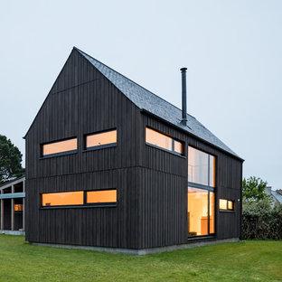Imagen de fachada de casa negra, urbana, de tamaño medio, de dos plantas, con revestimiento de madera y tejado a dos aguas