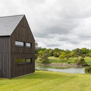 Foto de fachada de casa negra, urbana, de tamaño medio, de dos plantas, con tejado a dos aguas y tejado de teja de barro