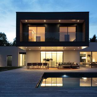 Aménagement d'une grand façade de maison blanche contemporaine à un étage avec un toit plat.