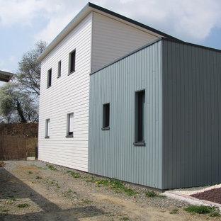 Imagen de fachada de casa multicolor, costera, de tamaño medio, de dos plantas, con revestimiento de madera, tejado de un solo tendido y tejado de metal