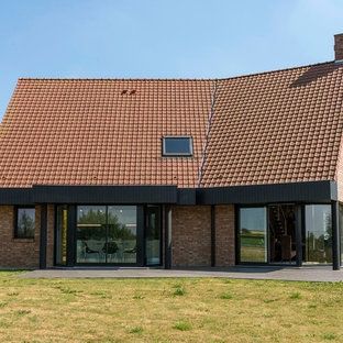 Aménagement d'une grand façade de maison rouge contemporaine à un étage avec un toit à deux pans et un toit en tuile.