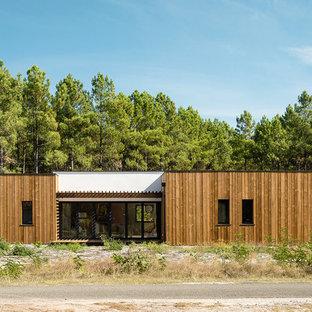 Cette image montre une façade en bois marron minimaliste de plain-pied avec un toit plat.