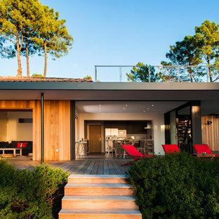 Idée de décoration pour une grand façade en bois marron marine de plain-pied avec un toit plat.