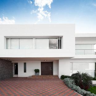Exempel på ett stort modernt vitt hus, med två våningar och platt tak