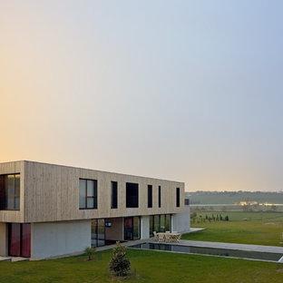 Réalisation d'une grande façade de maison design à un étage avec un toit plat et un revêtement mixte.