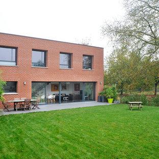Réalisation d'une façade en brique rouge design de taille moyenne et à un étage avec un toit plat.
