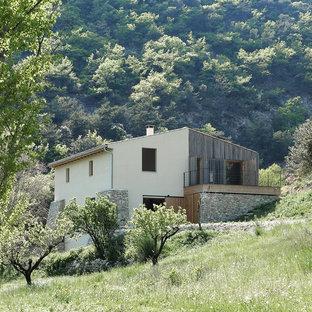 Imagen de fachada de casa marrón, escandinava, grande, de dos plantas, con revestimientos combinados, tejado a dos aguas y tejado de teja de barro