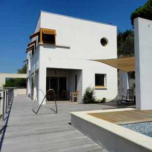Idées déco pour une façade de maison blanche moderne de taille moyenne et à un étage avec un toit plat.
