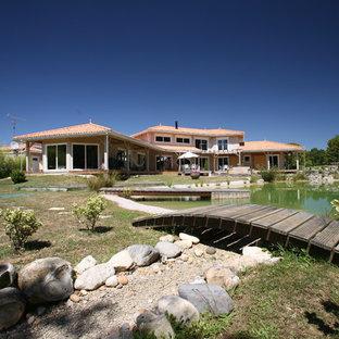 Aménagement d'une façade de maison beige méditerranéenne de taille moyenne et à un étage avec un toit à quatre pans.